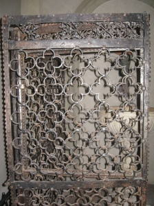 La griglia in ferro battuto che racchiude il fonte battesimale